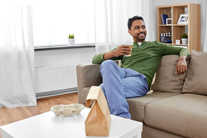 Indian man with takeaway coffee and food at home. Consumption and people concept - smiling indian man with takeaway coffee and food at home royalty free stock photo