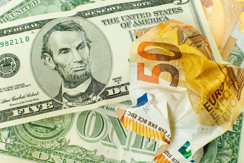 A conta amarrotada do euro 50 está sobre em dólares americanos Lincoln com sorrir forçadamente 5 de uma nota de dólar sobre amarr imagens de stock