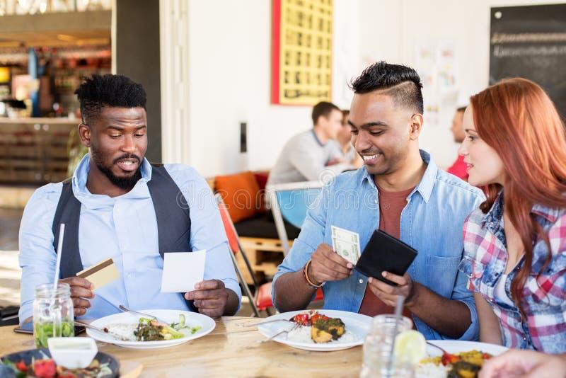 Conta pagando dos amigos felizes para o alimento no restaurante fotos de stock