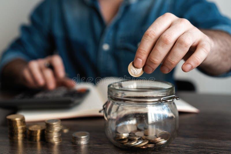 contabilidade da empresa com dinheiro da economia com a m?o que p?e moedas no conceito de vidro do jarro financeiro imagens de stock