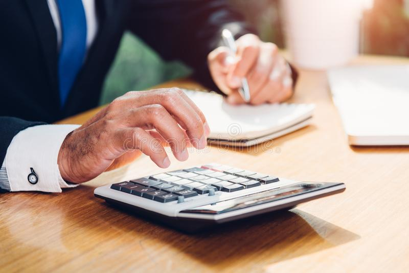 Contabilidade do homem de negócio usando o cálculo e o trabalho com portátil c imagens de stock royalty free