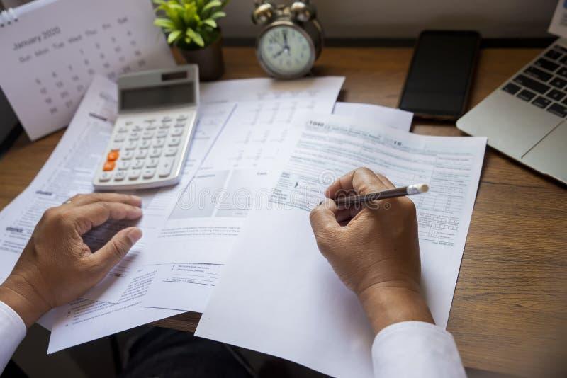 ,Contabilista está calculando o imposto anual da empresa imagem de stock