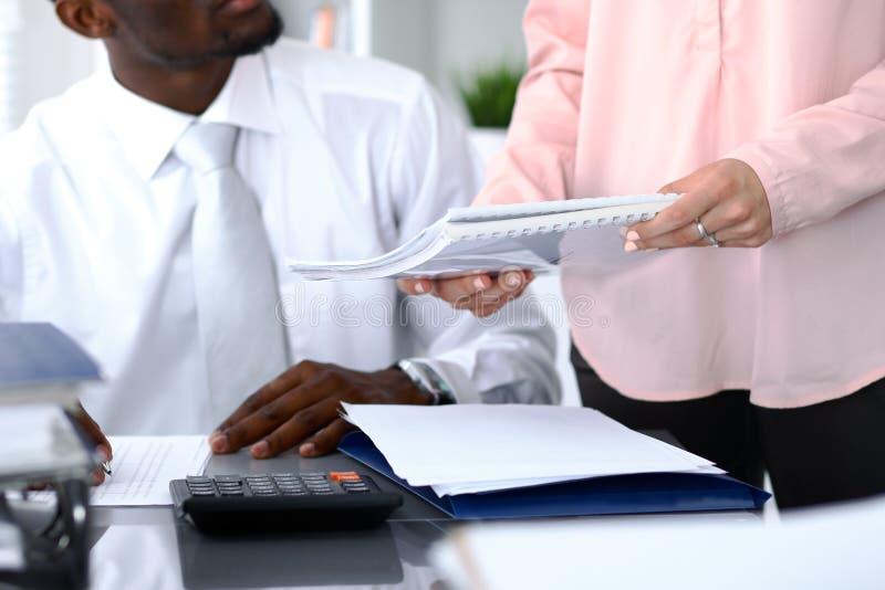 Contable afroamericana o inspector financiero que hace informe, calculando o comprobando la balanza Revenu interno imágenes de archivo libres de regalías