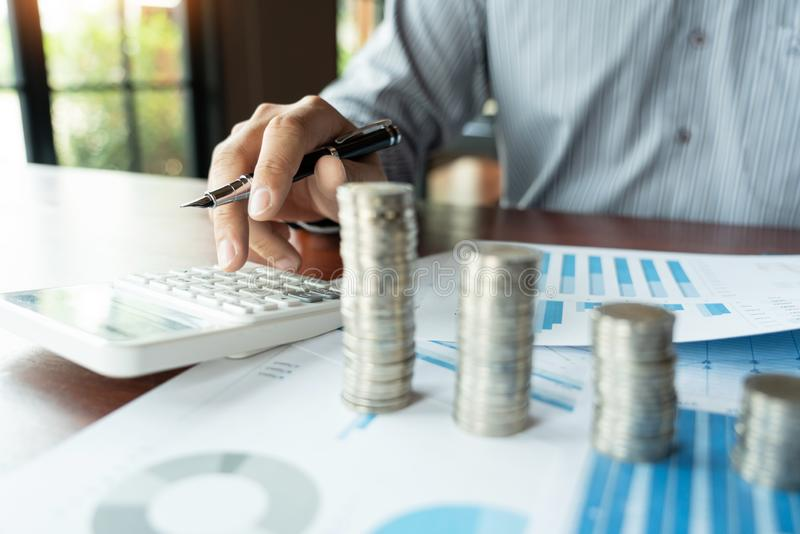 Contable Calculating del hombre de negocios en los documentos y la pila de monedas, la inversi?n de los datos de la pila del dine fotos de archivo libres de regalías
