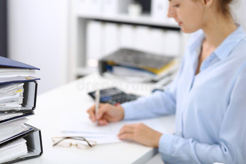 Contable de sexo femenino desconocida o inspector financiero que calcula o que comprueba la balanza, haciendo informe, primer int fotos de archivo