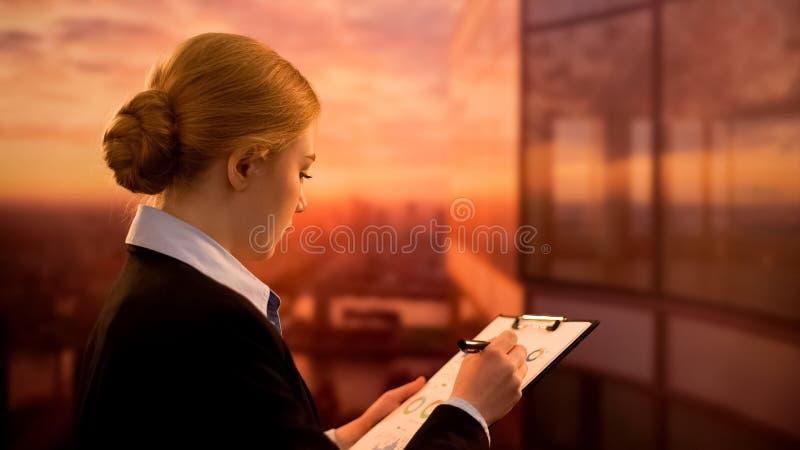 Contable de sexo femenino que comprueba el informe de la renta de la compañía, estrategia empresarial, tiempo de la puesta del so imagen de archivo