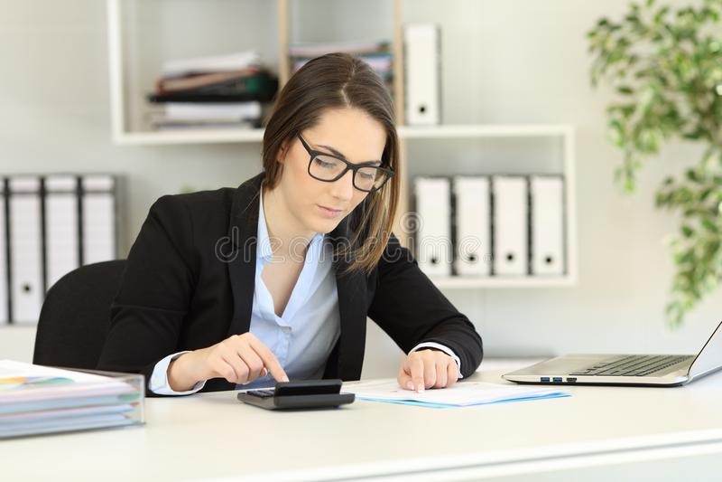 Contable que hace la contabilidad en la oficina imágenes de archivo libres de regalías