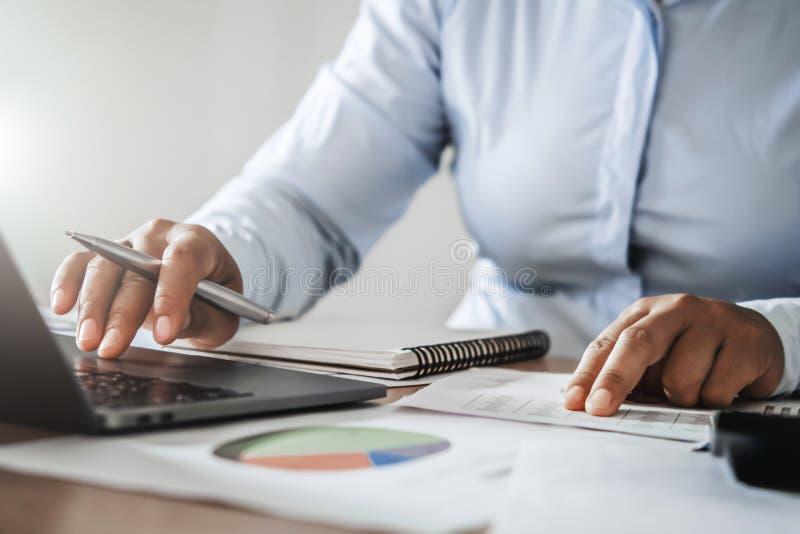 contable que trabaja en oficina usando el ordenador portátil del ordenador en el escritorio Concepto de las finanzas y de estad?s foto de archivo libre de regalías