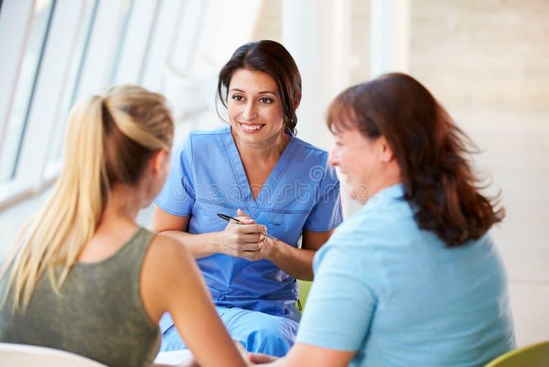 Contact d'infirmière avec l'adolescente et la mère images libres de droits