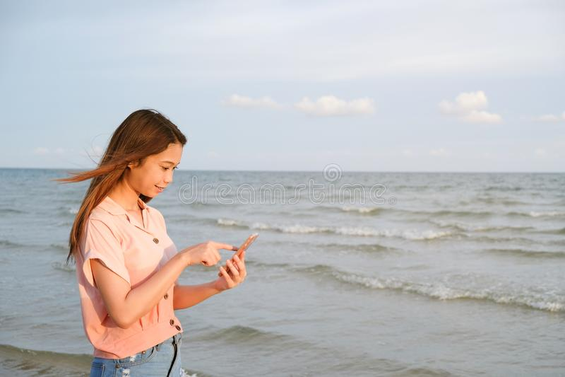 Contact de jeune femme au téléphone portable se tenant à la plage, concept de voyage d'été image stock