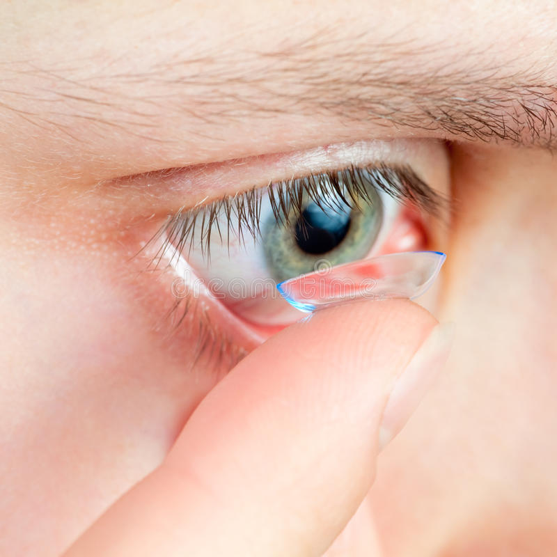 Contact lens. Young woman Inserting a contact lens closeup royalty free stock image