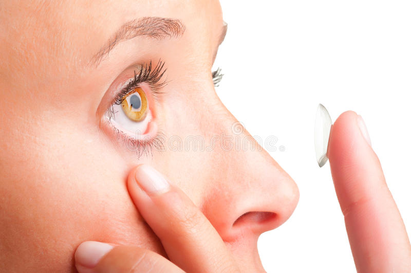 Contact Lens. Closeup of a woman inserting a contact lens in her eye stock photo