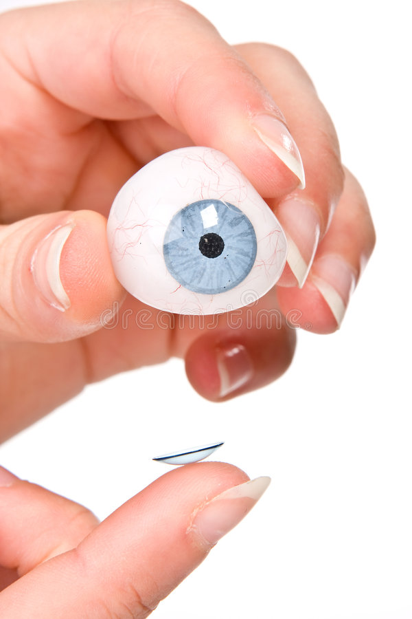 Contact lens. Finger putting a contact lens on an artificial eye stock photos