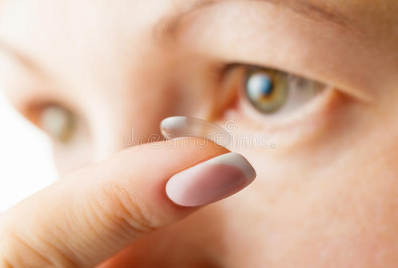 Contact lens. Female eye and contact lens. Focus on finger stock images