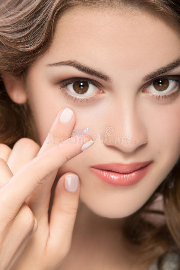 Contact lens. On finger of young woman looking on camera stock photography