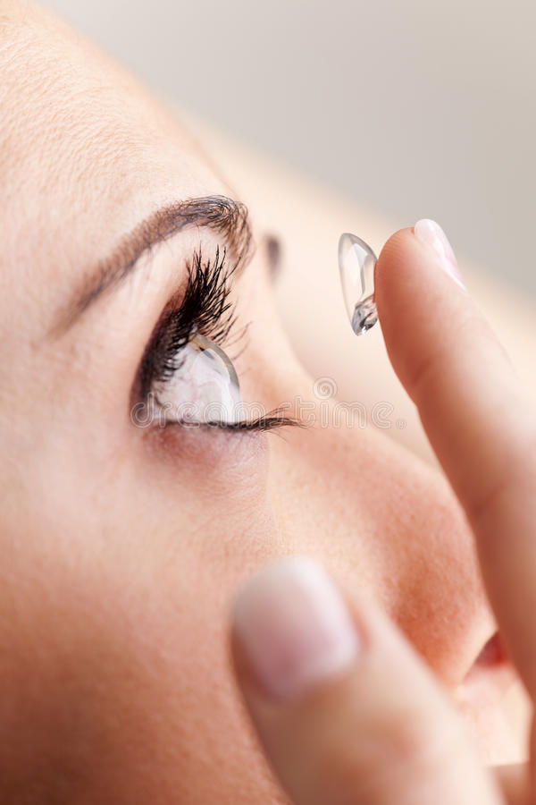 Contact Lenses. Woman putting on on contact lenses stock photography