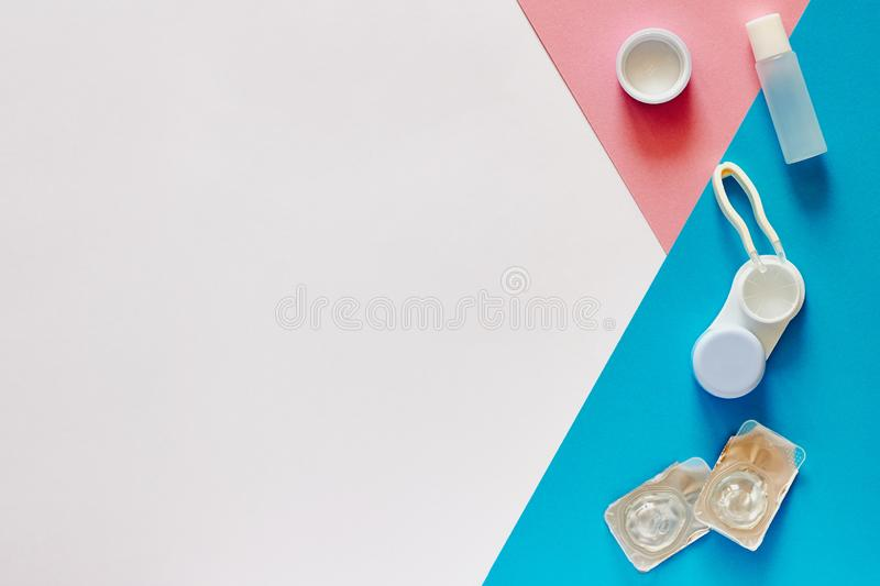 Contact lenses, case and accessories on pink, blue and white background. Eye health and care, eyesight and vision, ophthalmology. And optometry concept. Flat royalty free stock photo