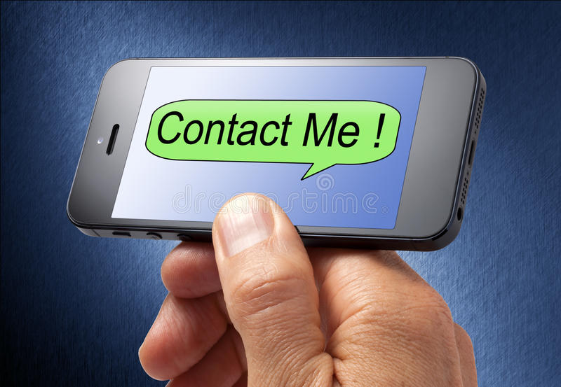 Contact Me Cell Phone. A hand holding a cell phone with contact me on the screen royalty free stock image