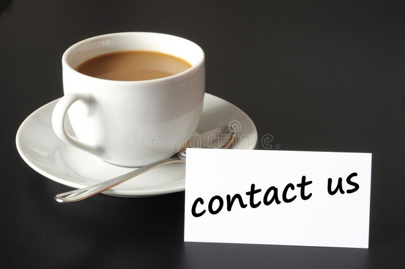Contact us. And coffee cup showing business support concept stock photo