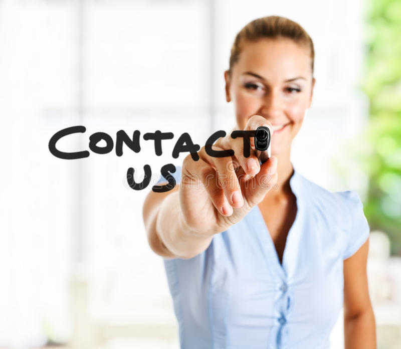 Contact us. Beautiful woman writing Contact us on the screen
