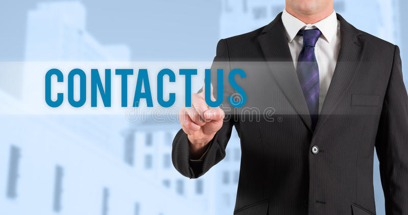Contact us against low angle view of city buildings. The word contact us and businessman in suit pointing finger against low angle view of city buildings stock photography