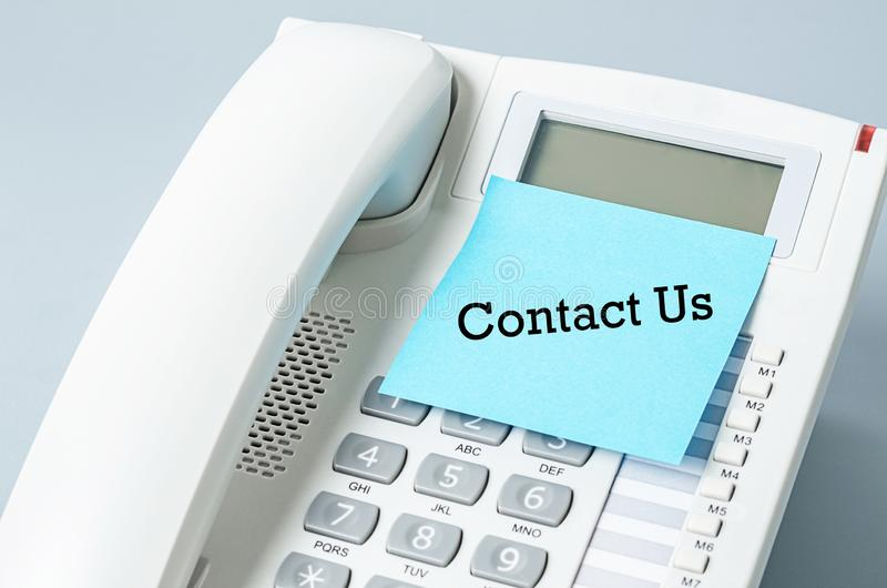 Contact us on blue sticky note. On the telephone stock photography