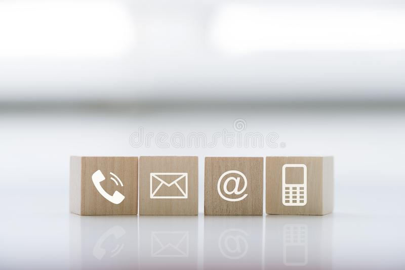 Contact us concept with wood block symbol telephone, mail, address and mobile phone. royalty free stock photos