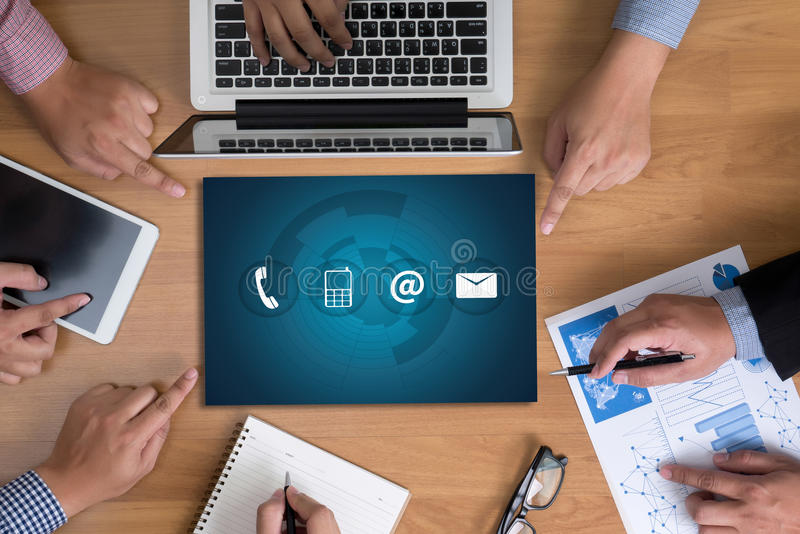 CONTACT US (Customer Support Hotline people CONNECT ). Business team hands at work with financial reports and a laptop, top view royalty free stock photos