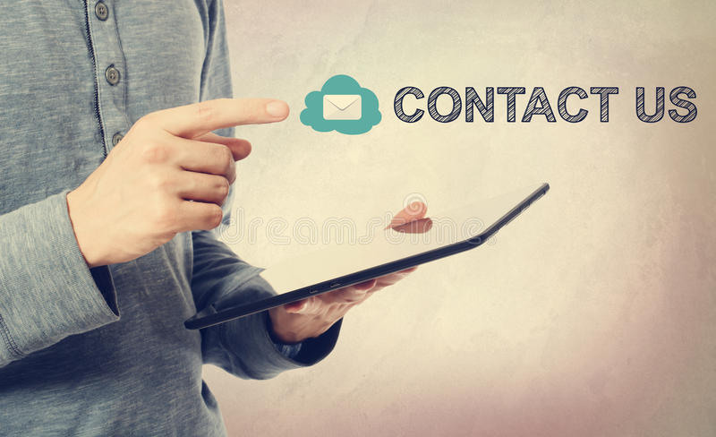 Contact Us message over a tablet computer. Young man pointing at Contact Us text over a tablet computer royalty free stock image