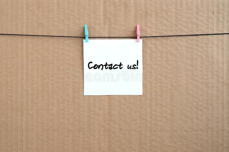 Contact us! Note is written on a white sticker that hangs with a stock images