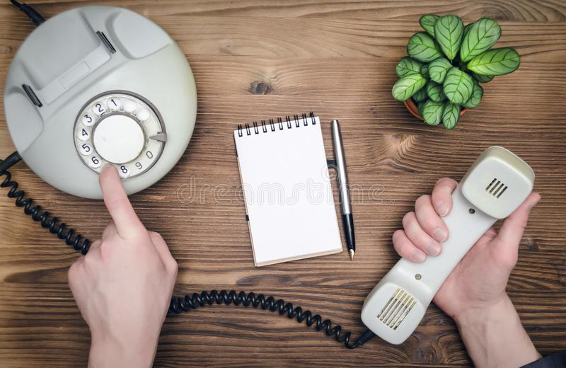 Contact us. Telephone in male businessman hands and notebook with copy space on office table. Contact us. Business conversation royalty free stock images