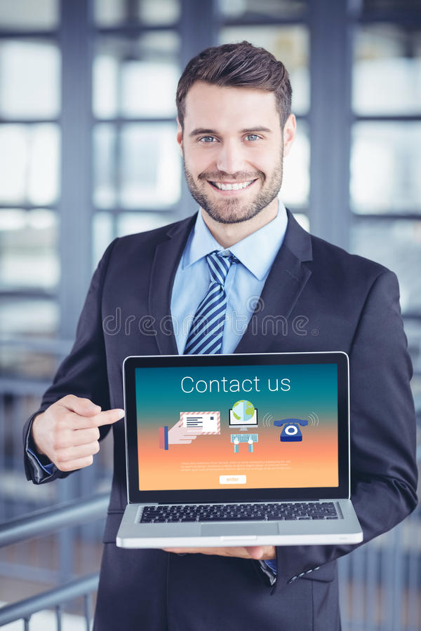 Composite image of contact us text with icons. Contact us text with icons against happy businessman showing laptop royalty free stock photo