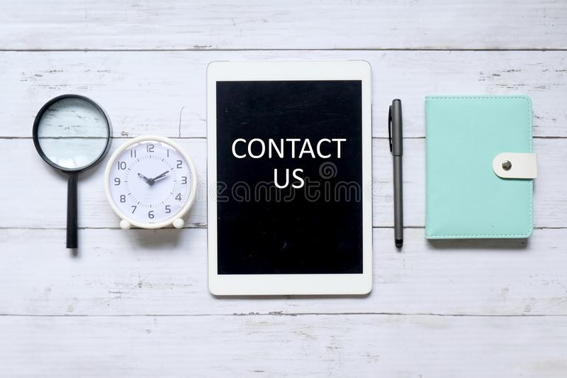 Contact us. Top view of magnifying glass,table clock,pen,notebook and tablet computer written with & x27; CONTACT US& x27; on white wooden background stock images
