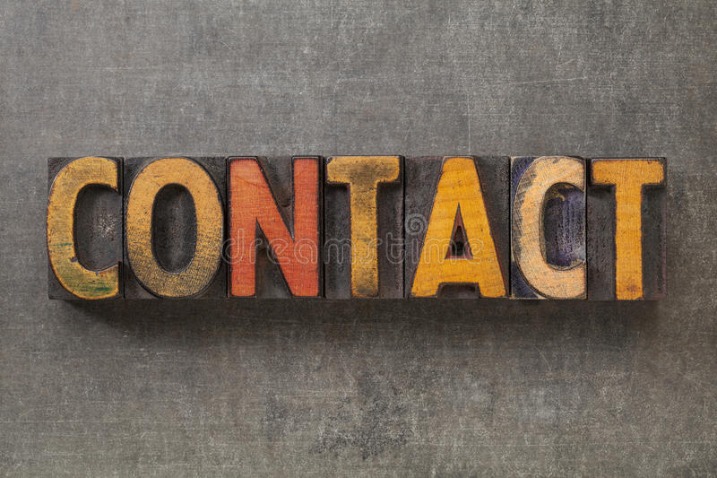 Contact word in wood type. Contact word in vintage letterpress wood type blocks against grunge metal background