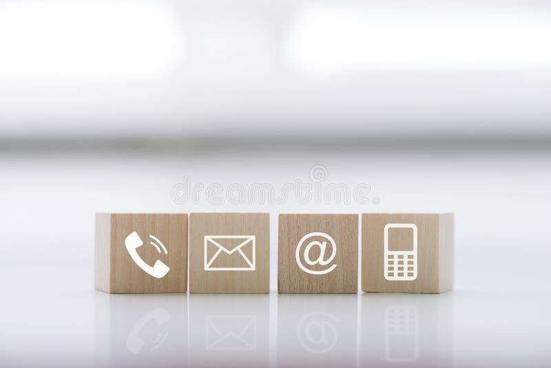 Contacte-nos conceito com o telefone, o correio, o endereço e o telefone celular do símbolo do bloco de madeira fotos de stock royalty free