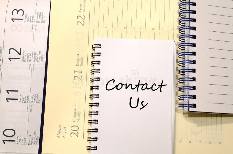 Contacte-nos escrevem no caderno fotos de stock royalty free