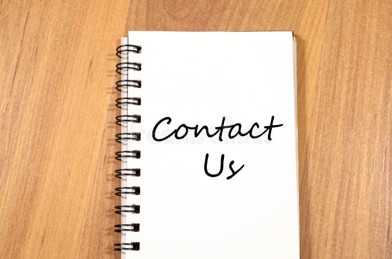 Contacte-nos escrevem no caderno imagens de stock