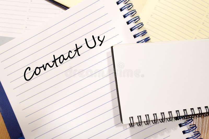 Contacteer ons schrijven op notitieboekje stock foto