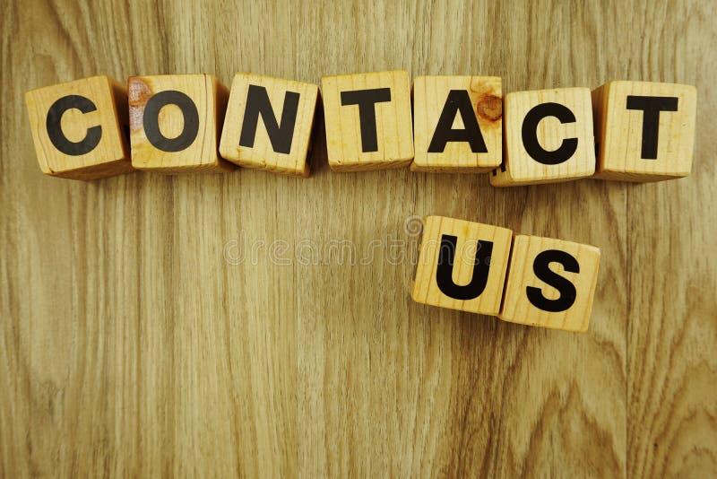 Contacteer ons woord van houten kubussen met brievenalfabet dat wordt gemaakt stock afbeelding
