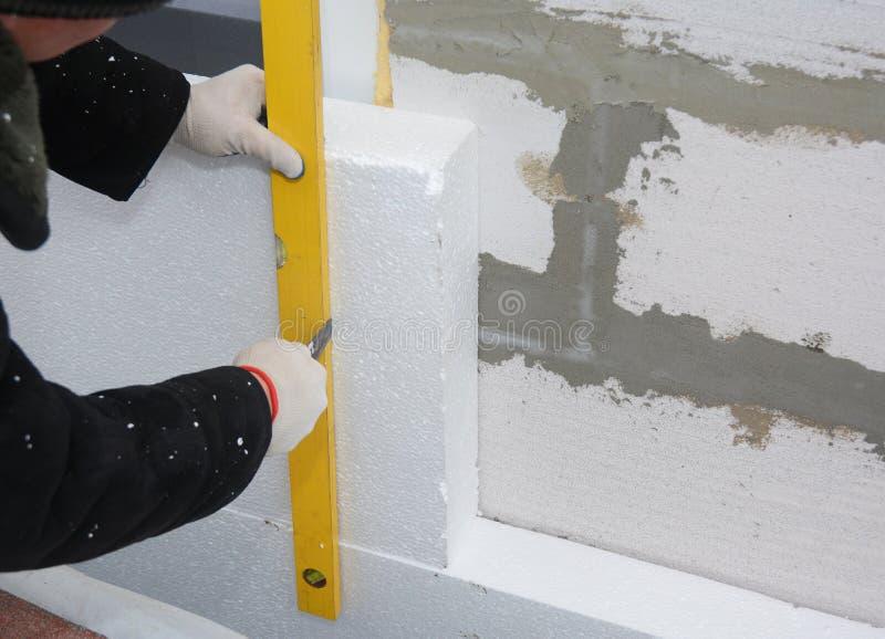 Contacteur installant l'isolation rigide de panneau de mousse de styrol sur le mur de maison pour l'économie d'énergie photographie stock libre de droits