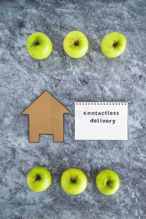 Contactless Delivery text on notepad among apples and with house icon concept of groceries shopping during quarantine or lockdown. The new normal after covid-19 stock photography