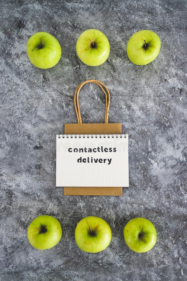 Contactless Delivery text on notepad among apples and with shopping bag concept of groceries shopping during quarantine or. The new normal after covid-19 royalty free stock images