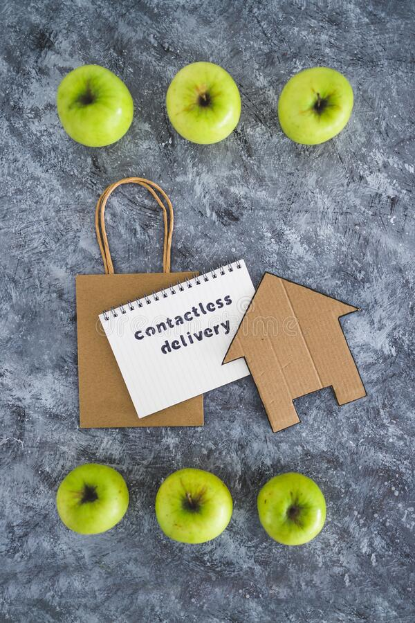 Contactless Delivery text on notepad among apples and with shopping bag and house icon concept of groceries shopping during. The new normal after covid-19 stock photos