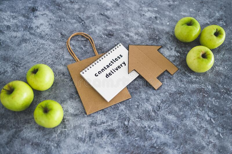 Contactless Delivery text on notepad among apples and with shopping bag and house icon concept of groceries shopping during. The new normal after covid-19 royalty free stock photo