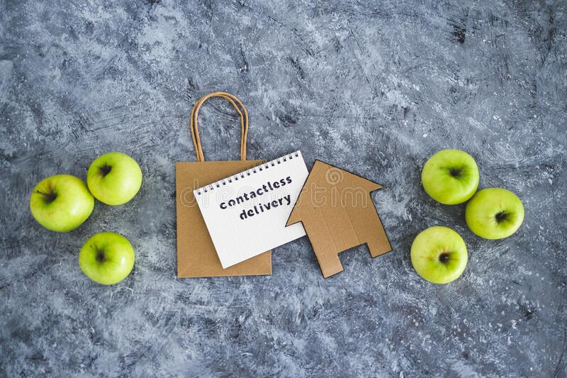 Contactless Delivery text on notepad among apples and with shopping bag and house icon concept of groceries shopping during. The new normal after covid-19 royalty free stock photography