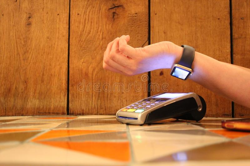 Contactless payment apple watch pdq background copy space with hand holding credit card to pay. Contactless payment watch apple pdq with hand holding credit card stock photography