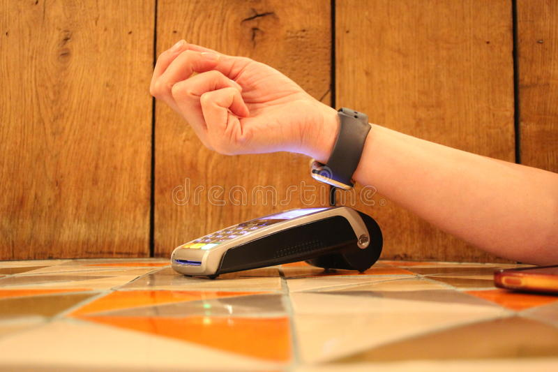 Contactless payment apple watch pdq with hand holding credit card to pay. Contactless payment watch apple pdq with hand holding credit card ready to pay stock photo