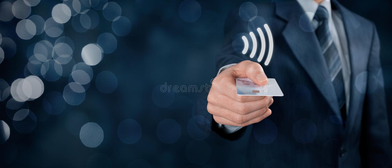 Contactless payment. Concept. Man pay with contactless credit card, virtual contactless symbol above card. Wide banner composition with bokeh in background royalty free stock photos
