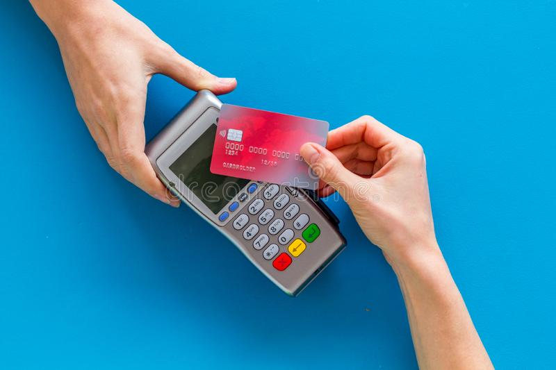 Contactless payment, paypass. Hand hold bank card near terminal on blue background top-down stock images