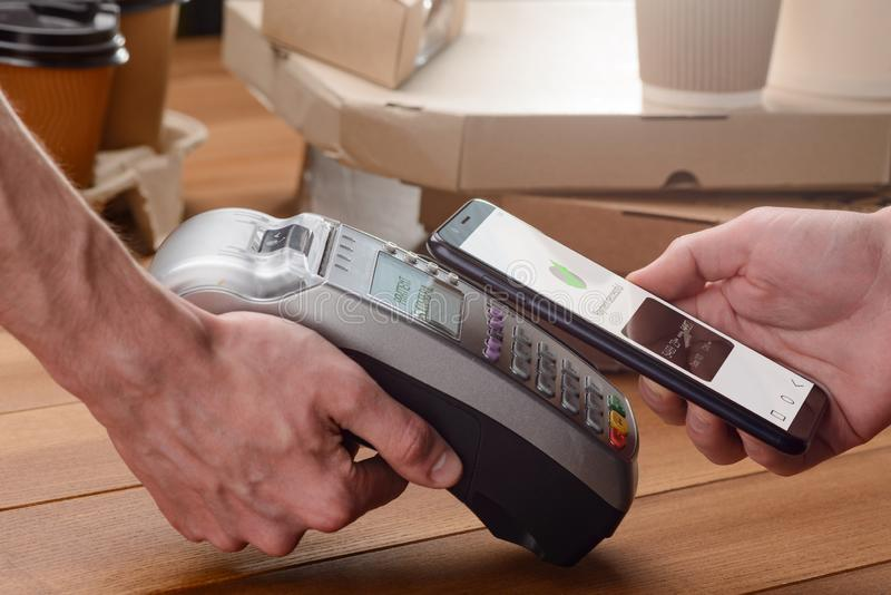Contactless payment with a phone. Close-up shot. Customer buying pizza and coffee and tapping his gadget to the terminal royalty free stock photos